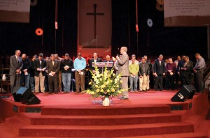 Evangelism Specialist Tim Gentry prays over All-State baptism leaders; SEC speakers included.