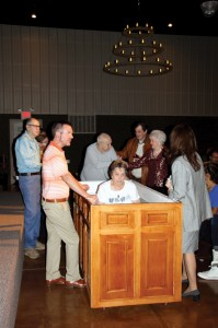 Justin Jester, pastor of Oklahoma City, Gateway officiates Mrs. Hurley's baptism with family and friends witnessing and supporting.