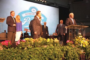 Hance Dilbeck, pastor of Oklahoma City, Quail Springs and newly-elected SBC 2nd vice president, with his wife, Julie, listen with newly-elected SBC President Ronnie Floyd, middle, to Frank Page, president and CEO of SBC Executive Committee, at podium, introduce the new SBC officers.