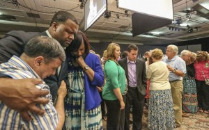 Roger Wall, left, embraces Dante and Schenita Randolph during a time of prayer for the 95 International Mission Board and North American Mission Board missionaries commissioned during a Woman's Missionary Union Celebration June 8 at the Baltimore Convention Center. Wall, pastor of Providence Baptist Church in Pageland, S.C., served in Durham, N.C., where the Randolphs serve as missionaries at Grace Park Church.  Photo by Bill Bangham.