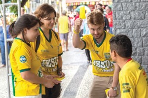 photo: Wilson  Hunter Student volunteer Grant Gilliam raises a yellow card—resembling what a referee uses to call a rule violation in a soccer match—to get the attention of a soccer fan near Rio de Janeiro's Maracana Stadium. Gilliam and his teammates, from left, Bianca Brandao and Stephanie Silva, a student at Oklahoma Baptist University, shared the Gospel before a World Cup match.