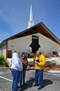BGCO Disaster Relief Director Sam Porter, right, visits with, from left, David Healey and Larry Dyer, members of Sand Springs, Keystone Hills, which was severely damaged by a twister March 25. The church auditorium in the background is essentially a total loss, Dyer said. (Photo: Bob Nigh)