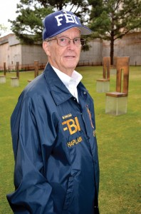Williams in his FBI chaplain jacket and cap stands among the Field of Empty Chairs, which memorializes those who perished. (Photo: Bob Nigh)