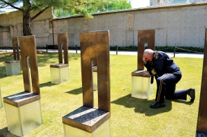 Jack Poe prays beside the memorial chair for Secret Service Agent Mickey Moroney, who was killed in the Murrah bombing (Photo: Bob Nigh)