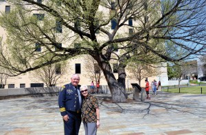 Jack and Phyllis Poe pose in front of The Survivor Tree, an American Elm that stood in the parking lot of the Journal Record Building, now the Oklahoma City National Memorial, shown in the background. (Photo: Bob Nigh)