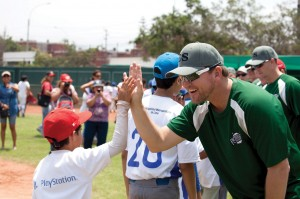 Tommy Phelps, former pitcher for the Florida Marlins during their 2003 World Series championship season, high-fives a local little leaguer during a baseball clinic in Lima, Peru. (Photo: Lina White/IMB)