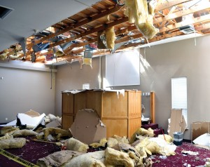 The interior of Sand Springs, Keystone Hills' worship center shows the destructive force of the tornado that hit the building; 6) a member of a chain saw crew trims smaller branches off a huge tree which fell on a residence in Sand Springs. (Photo: Bob Nigh)