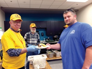 A job fair participant is served a hamburger from a DR volunteer.
