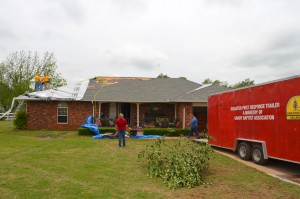 Disaster relief volunteers from Grady Baptist Association place tarps on the damaged roof of a home in Bridge Creek May 7. (Photo: Bob Nigh)