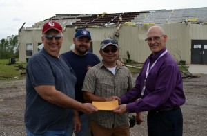 Bob Shelton, right, representing the Baptist General Convention of Oklahoma (BGCO), shakes hands with Ridgecrest Church Pastor David Rivers as he presents a check in the amount of $5,000 from BGCO Disaster Relief funds to Grady Association Director of Missions Chuck Utsler May 7. The money will go to the church , which had its children's ministry building, shown in the background, destroyed in a May 6 tornado, along with other buildings. Second from left is Ridgecrest's Children's Minister Derreck Fraysur. (Photo: Bob Nigh)