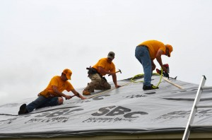 From left, Scott Cross, David Philpott and Paul Gustafson tarp the roof of a home in Bridge Creek. (Photo: Bob Nigh)