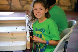 2) A camper works on a bracelet that can be used to share the Gospel (Photo: Chris Doyle)