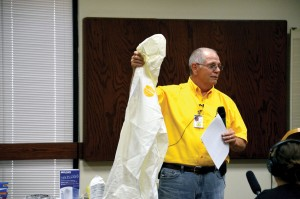Mud-out and flood recovery expert Richard Brown displays a plastic clothing protection suit as part of his presentation during the first of three training sessions he gave May 27 at Norman, Bethel (Photo: Bob Nigh)