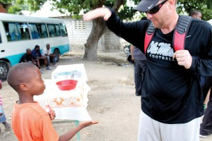 Ole Miss head football coach Hugh Freeze makes a new friend in Haiti during a mission trip joined by 11 players during this year's Spring Break. (Photos: Baptist Press)