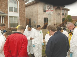 "Luter and his wife, Elizabeth, right, are prayed over before Oklahoma DR volunteers begin to ""mud-out"" their home in 2005. (Photo: Messenger File)"