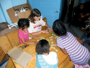 Bennett works with client children in the Friendship House to put together a puzzle. (Photo: Provided)