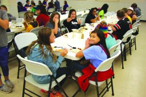 Campers enjoy fellowship over a meal at CrossTimbers.