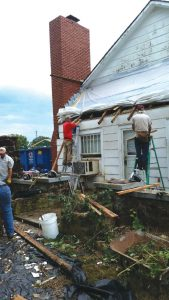Masham members put a roof on a neighboring house as a ministry of outreach.