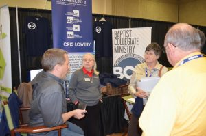 Chad Coleman, UCO BCM director, left, and Susanne Lillard, former BCM ministry assistant, second left, share about Baptist Collegiate Ministry at their booth during the 2015 BGCO Annual Meeting.