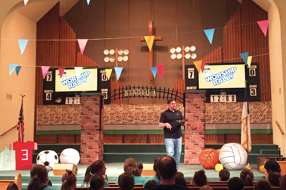 pastor-Bro.-Kelly-Russell-at-First-Baptist-Enid-leading-the-opening-of-our-Game-On-VBS